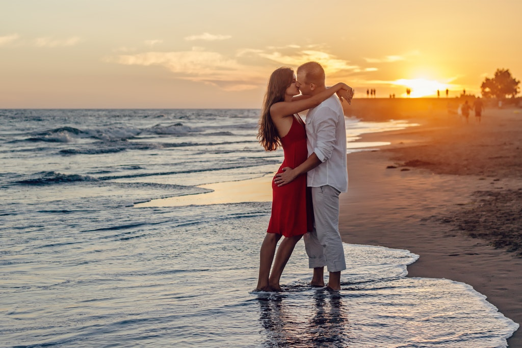 couple kissing in the beach at sunset