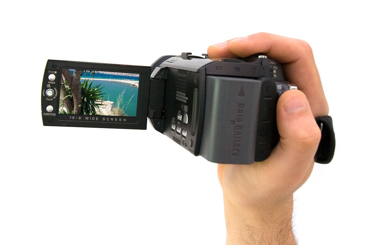 a hand holding a camcorder