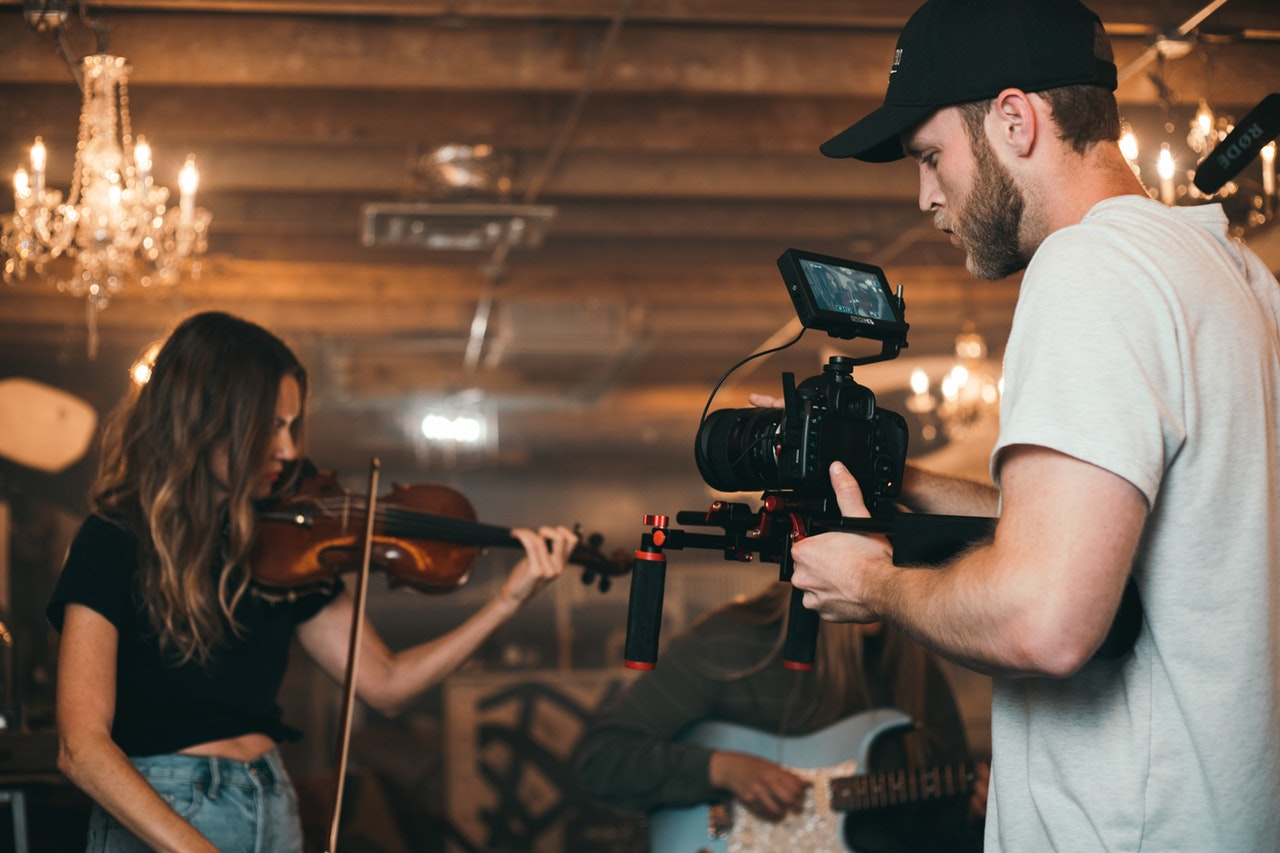 a videographer taking video on a woman playing a violin