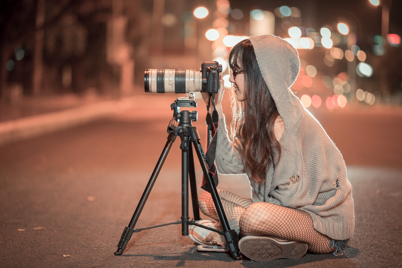 woman using a camera placed on a tripod