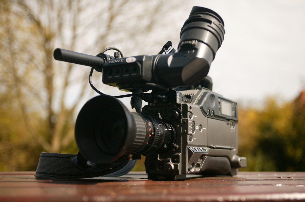 large camcorder placed on a wooden surface outdoors