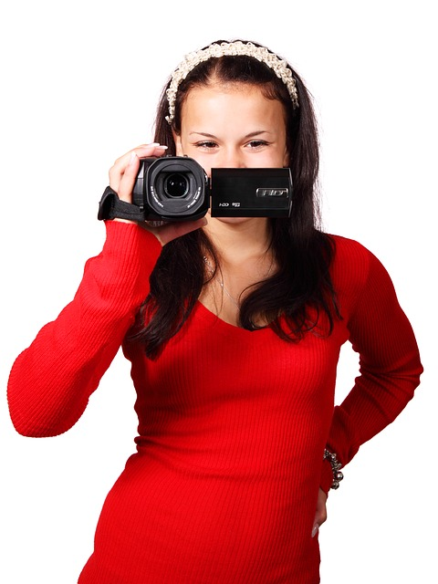 lady in red holding a HDcamcorder